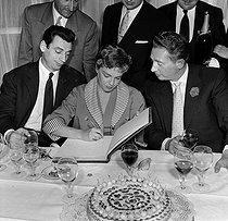 Charles Trenet (1913-2001), French singer-songwriter, celebrating his birthday at the restaurant of the Eiffel Tower with Yves Montand and Simone Signoret, signing the visitors' book. Paris, 1955. © Roger-Viollet
