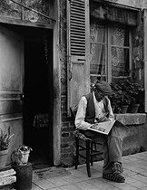 Man reading the newspaper sitting in front of his house. Semur-en-Auxois (Côte-d'Or), 1954. Photograph by Janine Niepce (1921-2007). © Janine Niepce / Roger-Viollet