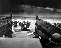 World War II. Landing on the coast of France under heavy Nazi machine gun fire are these American soldiers, shown just as they left the ramp of a Coast Guard landing boat. June 6, 1944. © US National Archives / Roger-Viollet