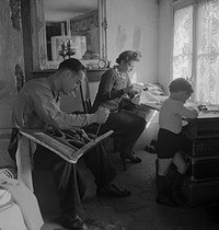 Father and mother soing upholstery work and their son. France, 1937-1940. © Gaston Paris / Roger-Viollet