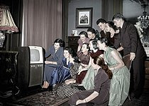 Young people watching French television, during the transfer of power between the presidents Vincent Auriol and René Coty. Colourized photo. January 1954. © Roger-Viollet