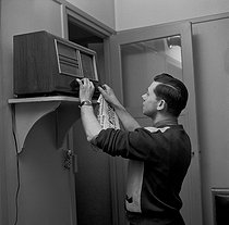 Workers' family life. Father setting the radio. Paris, 1952. © Jacques Rouchon / Roger-Viollet