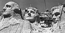 Gutzon Borglum (1867-1941). Ouvriers travaillant sur les visages du Mont Rushmore représentant quatre hommes d'Etat américains : George Washington, Thomas Jefferson, Theodore Roosevelt et Abraham Lincoln. Celui de Théodore Roosevelt (1838-1919) est caché par les échafaudages. Dakota du Sud (Etats-Unis), vers 1938. © Underwood Archives / The Image Works / Roger-Viollet