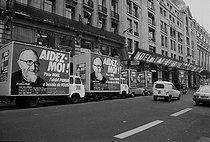 """Billboard trucks for Abbé Pierre's campaign, organised with the aid of """"France-Soir"""", for Christmas, in front of the newspaper's head office. Paris, December 1984. © Carlos Gayoso / Roger-Viollet"""