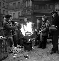 Brazier at the Halles market, place Sainte-Opportune. Paris, January 1954. © Roger-Viollet