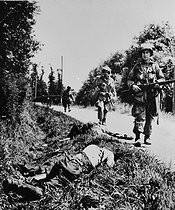 World War II. Front of Normandy. Paratroopers of the US Army walking by the corpse of a German soldier, on June 23, 1944. © Roger-Viollet