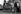 """Rue Gît-le-Coeur, au coin du Quai des Grands-Augustins. De g. à dr. : Tove, Eunice Richards, Stella Tohl, Keith, Ken Tindall et """"Cyclops"""" Lester. La charrette à bras fut empruntée au  """"charbonnier"""" local pour aller chercher la malle de Tindall à la librairie Mistral. Paris, début des années 1960. Photographie d'Harold Chapman (né en 1927). © Harold Chapman / TopFoto / Roger-Viollet"""
