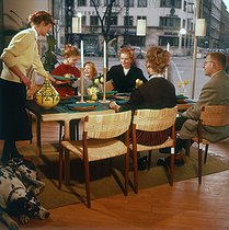 Living shop window. Family sitting at the table, eating in a dining room, around 1960-1965. © Roger-Viollet