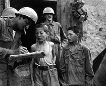 Korean War (1950-1953). Two North Korean boys, serving in the North Korean Army, taken prisoner in the Sindang-dong area by elelments of the 389th Inf. Regt., are interrogated by U.S. soldier shortly after their capture. September 18, 1950. (Army) © US National Archives / Roger-Viollet