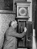 Homme remontant une horloge.     © Roger-Viollet