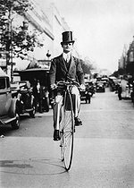 Man dressed in a 1900-suit and riding a penny-farthing, advertising for a Parisian music hall. Paris, 1934. © Jacques Boyer/Roger-Viollet