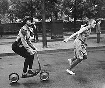 """Student celebration in the district of Montparnasse. """"Tchouky"""", Corsican dancer, drawn by Claude, French painter, on a scooter. Paris. Photo : Stettner. © Collection Roger-Viollet / Roger-Viollet"""