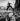 Homme traversant la rue en sautant au-dessus de tas de neige. Danemark, 1958.  © Erik Petersen/Polfoto/Roger-Viollet