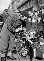 World War II. Robert Oubron (1913-1989), French racing cyclist, taking a look at an electric bicycle. Paris. 1941. © LAPI/Roger-Viollet