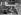 """Jean-Pierre Mocky (1929-2019), acteur et réalisateur français, dirigeant Charles Aznavour et Jacques Charrier dans une scène de son film """"Les Dragueurs"""". France, février 1959. © Bernard Lipnitzki / Roger-Viollet"""