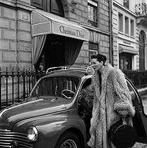 Lucky, French model, in her Renault 4CV car, in front of Christian Dior's boutique. Paris, 1950's. © Jacques Rouchon/Roger-Viollet