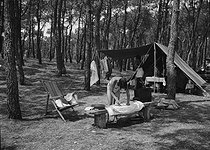 Young woman camping and ironing her linen in front of her tent. Les Sables-d'Olonne (Vendée). 1937. © Roger-Viollet