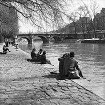 Relaxing on the banks of the river Seine, quai du Louvre, near the Pont Neuf. Paris, 1955-1960. © Oswald Perrelle/Roger-Viollet