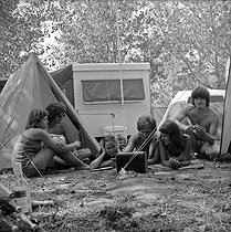 Young people listening to the radio with a transistor in a camping site. © Roger-Viollet