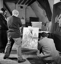 Pablo Picasso (1881-1973), Spanish painter and sculptor, from behind on the left, in his studio, rue des Grands-Augustins. Paris (VIth arrondissement), November 1944. © Pierre Jahan / Roger-Viollet
