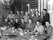 Guerre 1939-1945. Correspondants américains et officiers de l'armée prenant la pose après un dîner. Au premier rang de g. à dr. : Capitaine Henry Kelliher, Collie Small du United Press, Capitaine Ron Wright, Général de division Hort S Vandenberg, Général de division Ellsworth Quesada, et Stanley Frank du New York Post. Debout de g. à dr. : G Mancuso, photographe de la US Signal Corps, Capitaine Sacha Ballas, Austen Lake du Boston American, Rel Moore du Trans-Radio News, Bill Davidson du Yank, Hoiward Whitman du NY Daily news et Carlyle Holt du Boston Globe. France, 4 septembre 1944. © TopFoto / Roger-Viollet