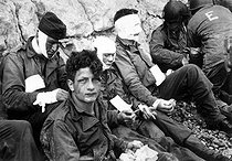 World War II. American assault troops of the 16th Infantry Regiment, injured while storming Omaha Beach, wait by the chalk cliffs for evacuation to a field hospital for further medical treatment. Colleville-sur-Mer, Normandy, France. June 6, 1944. © US National Archives / Roger-Viollet