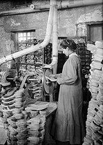World War I. Woman working at producing trench clogs. Soles pumiced by grindstone.   © Jacques Boyer/Roger-Viollet