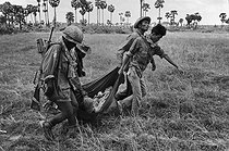 Soldiers evacuating another soldier wounded by the Khmer Rouge. Cambodia, 1974. © Françoise Demulder / Roger-Viollet