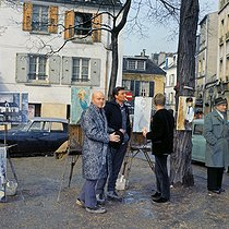 Painters and onlookers at the place du Tertre, in the district of Montmartre. Paris (XVIIIth arrondissement), 1960's. © Collection Roger-Viollet / Roger-Viollet