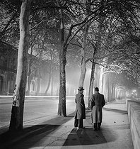 Avenue de Tokyo by night, two men walking, trees, Paris (XVIth arrondissement). 1938. Photograph by Roger Schall (1904-1995). © Roger Schall / Roger-Viollet