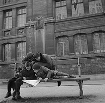 """Children reading """"Le Journal de Mickey"""", French weekly comics magazine, on a bench. France, 1950's. Photograph by Janine Niepce (1921-2007). © Janine Niepce/Roger-Viollet"""