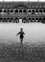 Little boy in the courtyard of the Invalides. Paris (VIIth arrondissement), 1953. Photograph by Janine Niepce (1921-2007). © Janine Niepce/Roger-Viollet