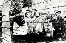 World War II. Jewish children survivors of Auschwitz with nurse behind barbed wire fence. Photo taken by Russian photographerduring making of a film about liberation of the camp.Children were dressed up by the Russians with clothing from adult prisoners. Auschwitz, Poland, February 1945. Galerie Bilderwelt.       BIL-AU 02 © Bilderwelt / Roger-Viollet