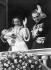 Grace Kelly (1929-1982), princesse de Monaco, et son époux Rainier III de Monaco (1923-2005), présentant leur fille Caroline (née en 1957), depuis le balcon du palais de Monaco (Principauté de Monaco), avril 1957. © Ullstein Bild/Roger-Viollet