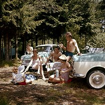 Camping in the forest. Family having a picnic near their cars, Glas Isar T700 models. Germany, 1950's-1960's. © Roger-Viollet