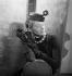 """Bibi en paille Suzanne Talbot, garni d'une fleur et d'une voilette. Photographié pour le magazine """"Fémina"""". Paris, janvier 1937. © Boris Lipnitzki/Roger-Viollet"""