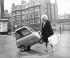 Jeune femme soulevant la Peel P50, voiture la plus petite du monde, pesant à peine 59 kg. Londres (Angleterre), 8 novembre 1962. © PA Archive/Roger-Viollet
