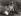 """""""Les mots de l'amour"""". Jeune couple assis sur l'herbe, l'homme jouant de l'accordéon. Italie, 1947-1948. © Vincenzo Balocchi/Alinari/Roger-Viollet"""