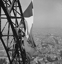 French flag on the Eiffel Tower. Paris, 1951. © Roger-Viollet