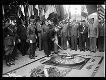 """U.S. officer rekindling the Flame at the Tomb of the Unknown Soldier for Independence Day. Ceremony in the presence of  Henri Gouraud (1867-1946), French General, and William C. Bullitt (1891-1967), American ambassador to France. Paris (VIIIth arrondissement), on July 4, 1939. Photograph from the collections of the newspaper """"Excelsior"""". © Excelsior – L'Equipe/Roger-Viollet"""