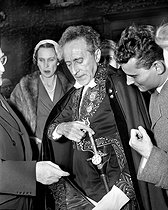 Jean Cocteau (1889-1963), French writer, playwright and director, greeted at the French Academy, showing his academician sword. Behind him : Queen Marie-José of Belgium (1906-2001). Paris, October 20, 1955. © Roger-Viollet