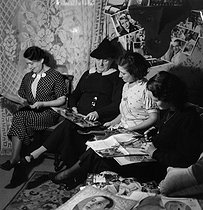 Fans of Tino Rossi (1907-1983), French singer and actor, looking at photographs from their collections. France, circa 1940. © Gaston Paris / Roger-Viollet