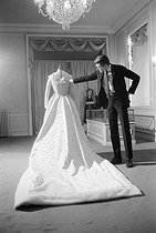 Yves Saint Laurent (1936-2008), French fashion designer, and the wedding dress of Farah Diba, Empress of Iran. December 1959. © Bernard Lipnitzki / Roger-Viollet