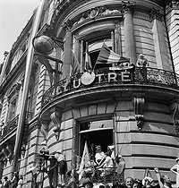"World War II. Liberation of Paris. Crowd at the building of ""Le Figaro"" newspaper, at the roundabout of the Champs-Elysées, attending the parade for the victory celebration. Paris (VIIIth arrondissement), on August 26, 1944. Photograph by Jean Roubier (1896-1981). © Fonds Jean Roubier/Roger-Vio"