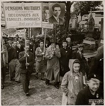 Demonstration for the payment of military pensions for the families of immigrants who died for France. Man holding a portrait of Missak Manouchian (1906-1944), Armenian poet and resistance fighter who died executed by the German army. © Archives Manouchian / Roger-Viollet
