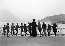 An abbot with children during a summer camp on the edge of a lake. Annecy (France), 1921. © Roger-Viollet