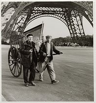 World War II. Two men pulling a cart loaded with a painting, under the Eiffel Tower, Paris (VIIth arrondissement). 1941. Photograph by Roger Schall (1904-1995). Paris, musée Carnavalet. © Roger Schall / Musée Carnavalet / Roger-Viollet