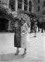 Mode aux courses. Robe de mousseline avec fleurs, ombrelle et robe boutonnée, manteau demi-saison. Paris (XVIème arr.), hippodrome d'Auteuil, 1926. © Maurice-Louis Branger/Roger-Viollet