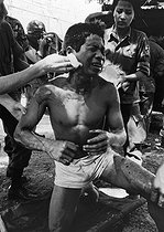 Wounded soldier treated by his comrades. Cambodia, 1975. © Françoise Demulder / Roger-Viollet