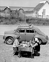 Couple eating at a table in front of a 4CV car. Camargue (France), 1954. © Roger-Viollet